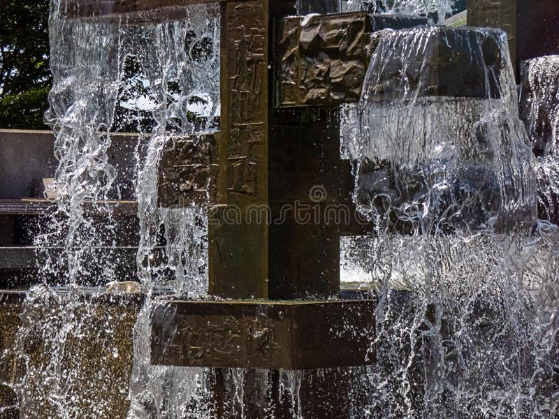 Decorative metal fountain with falling clear water stock photography