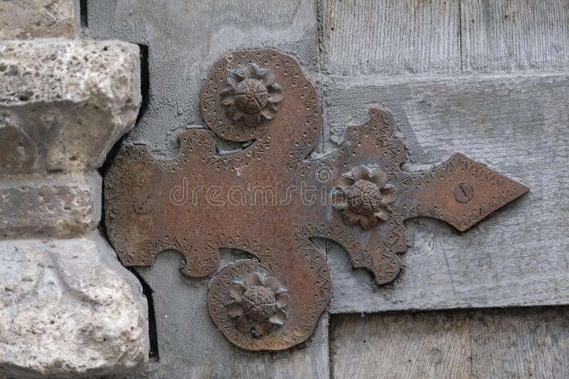 Decorative old forged hinge on a wooden door royalty free stock photography