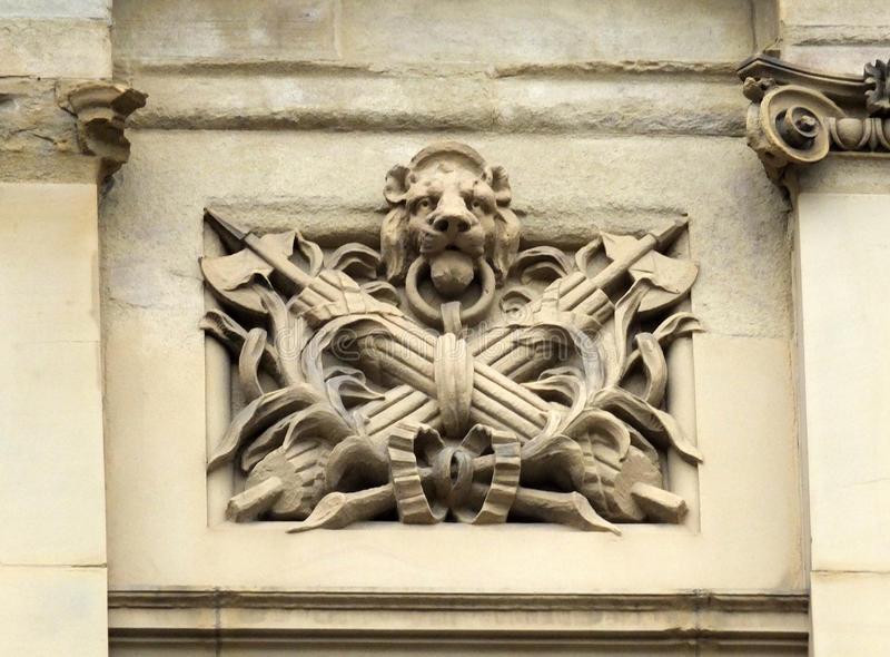 Decorative old stone carving of a lions head. Worn decorative old stone carving of a lions head fasces and palm leaves on halifax town hall with surrounding stock photo