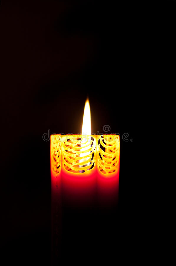 Decorative orange candle burning in the dark royalty free stock photography