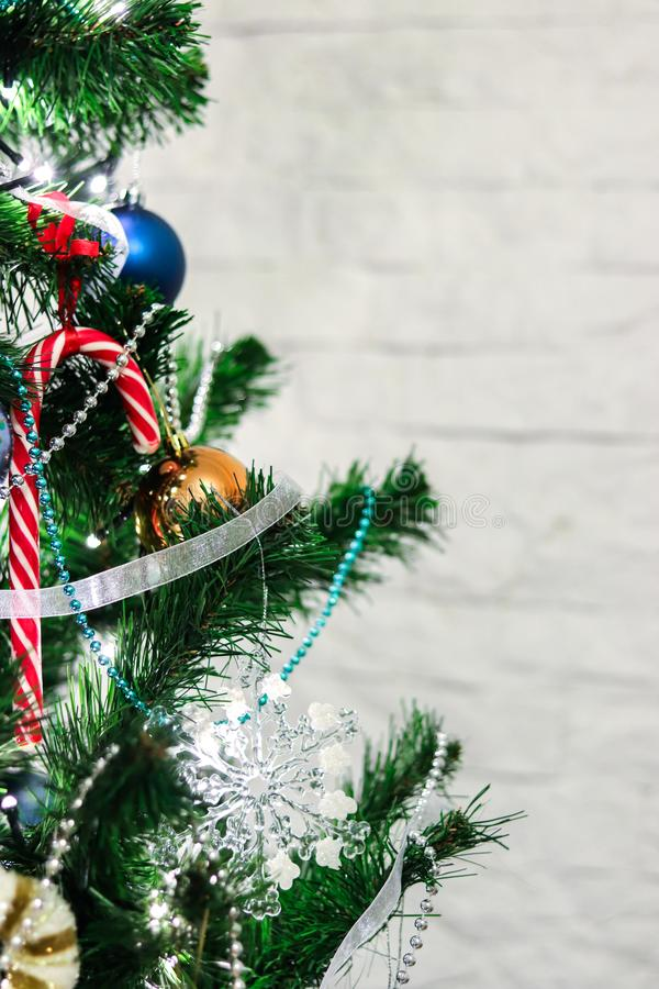 Decorative ornaments christmas tree with colorful toys and candy cane on white brick wall background with space for text royalty free stock photos