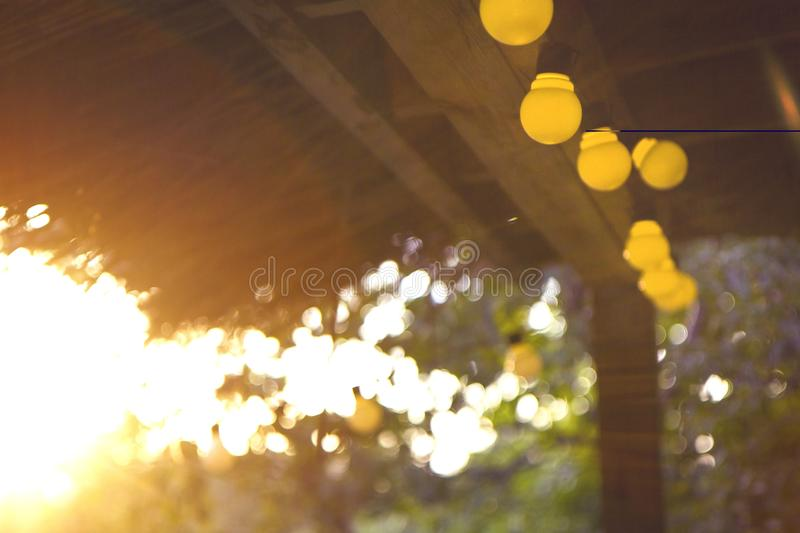 Decorative outdoor string lights hanging on the porch at the sunset.  stock image