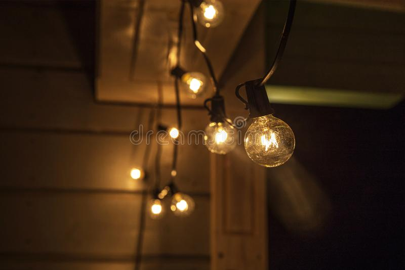 Decorative outdoor string lights hanging on tree in the garden at night time stock image