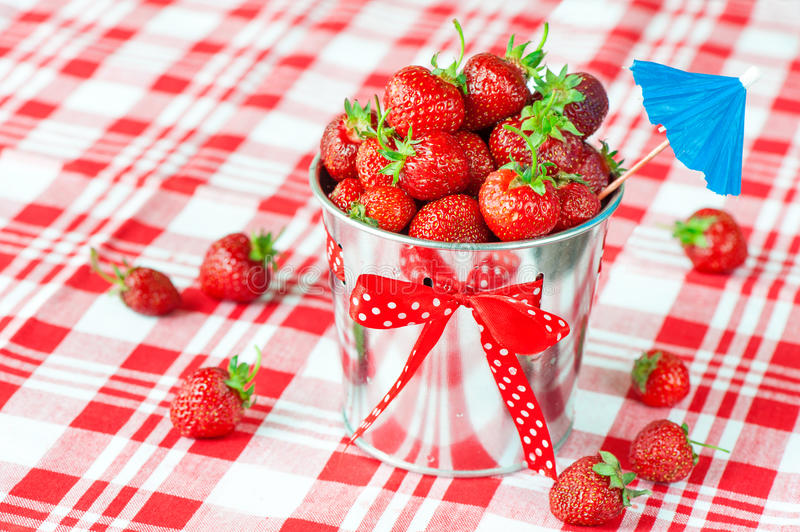 Decorative pail full of generous crop of ripe fresh juicy gourmet strawberry. royalty free stock images