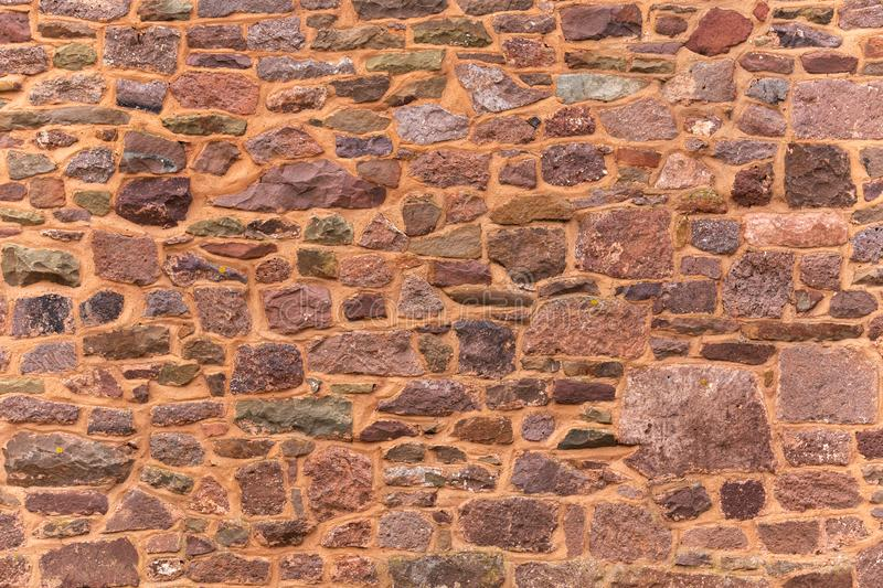 Decorative Pattern of ancient red stone wall background, texture. random size rock wall royalty free stock images