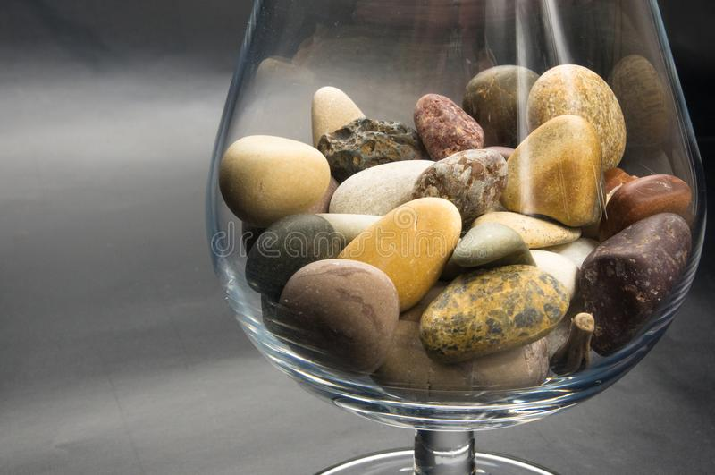 Decorative pebbles in glass containers. Multicolored decorative pebbles in glass containers on a black background royalty free stock photography