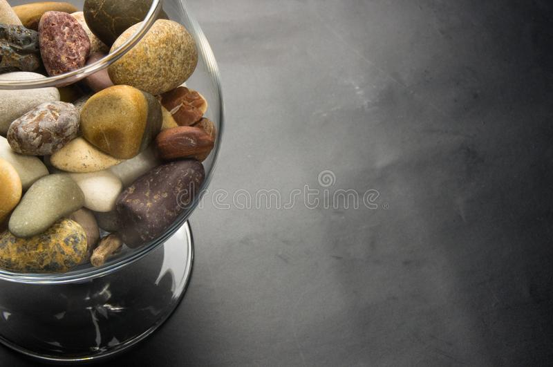 Decorative pebbles in glass containers. Multicolored decorative pebbles in glass containers on a black background stock photography