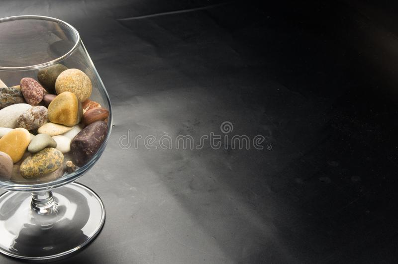 Decorative pebbles in glass containers. Multicolored decorative pebbles in glass containers on a black background stock photo