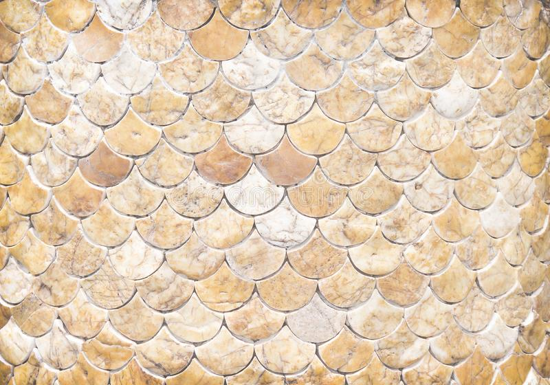 Decorative pieces of marble texture on concrete wall  in many layer fish  scale shaped patterns  , horizontal background. Close up Decorative pieces of marble royalty free stock photography