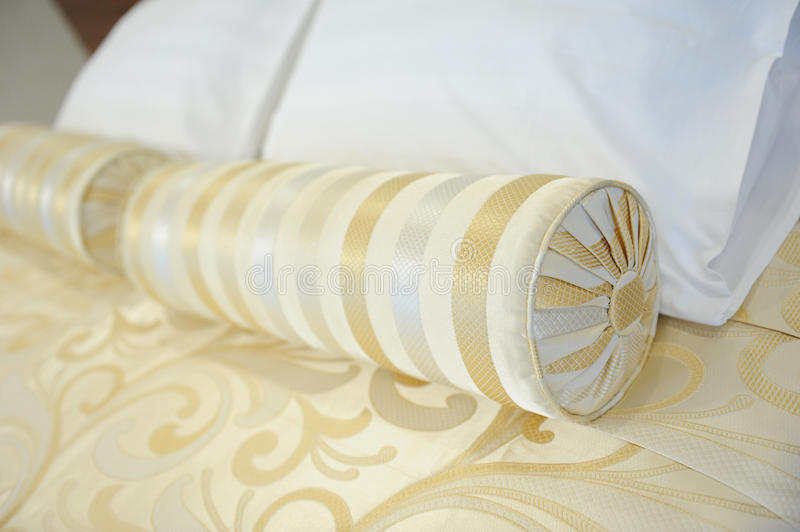 Decorative pillow-cushion of golden fabric on the bed. Closeup royalty free stock photography