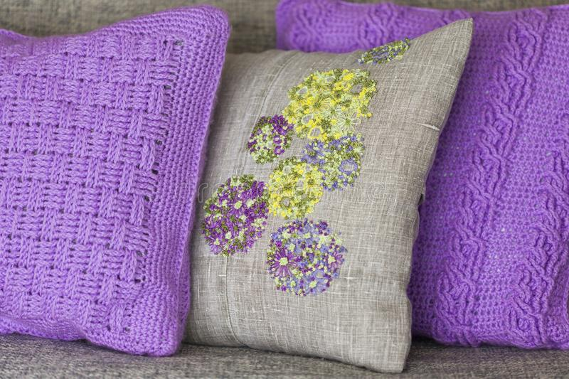Decorative pillows - knitted violet with braids pillow and pillow made of linen fabric with colorful embroidery stock photo