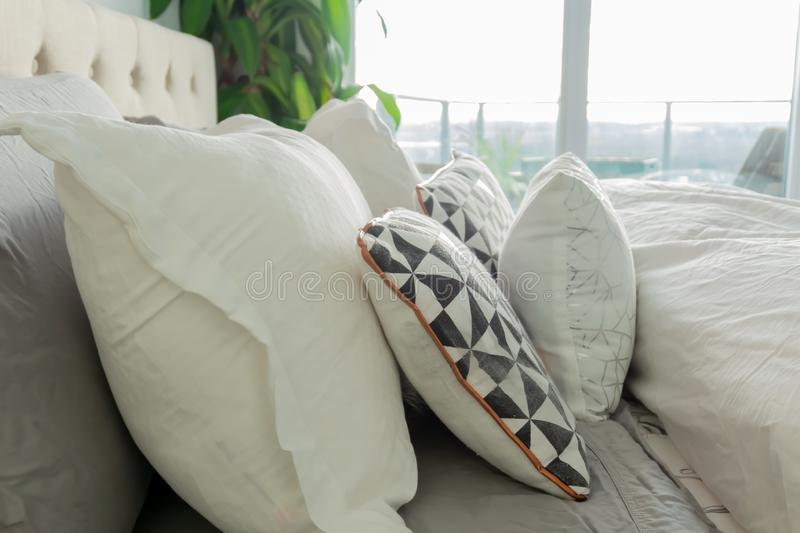 Decorative pillows on a real bed, inside an authentic home. White bedding with geometric pattern accents. Comfortable bed depictin. G relaxation stock photo