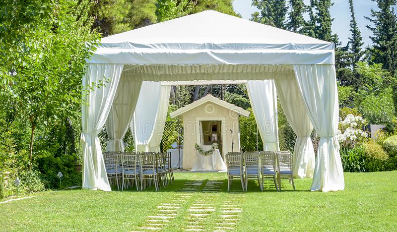 Decorative place for ceremonies or entertainments. Outdoor reception under tents and trees. Decorative place for ceremonies or entertainments.Outdoor reception royalty free stock image