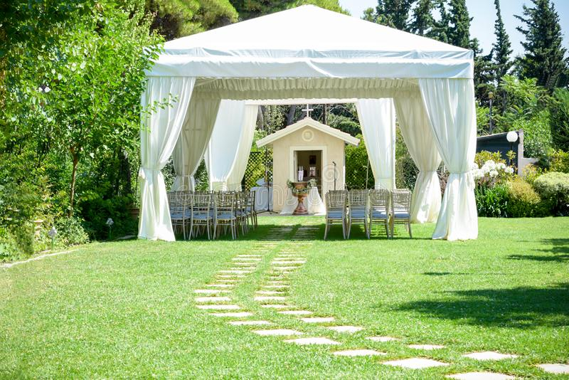 Decorative place for ceremonies or entertainments. Outdoor reception under tents and trees royalty free stock photos