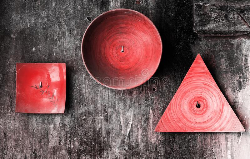 Decorative plates of various shapes on old grunge textured wall. Abstract living coral color toned vintage background stock photography