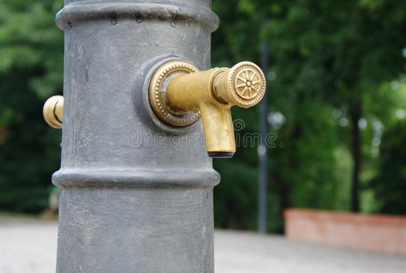 Decorative public tap with drinkable water. Decorative simple and new golden public metallic tap with drinkable water in the early morning after rain in the park royalty free stock image