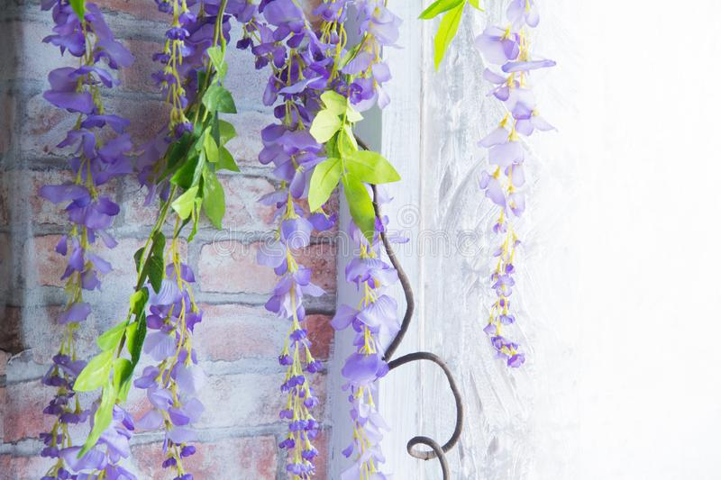 Decorative purple flowers near the winter frozen window on the background of a brick wall.  stock photography