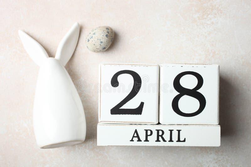 Decorative rabbit, wooden calendar and quail egg. One ceramic white decorative rabbit, wooden calendar with date of April 28 and quail egg on neutral background stock photo