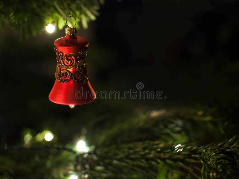 Decorative red bell with shiny ornaments hanging on christmas tree with lights in background royalty free stock image
