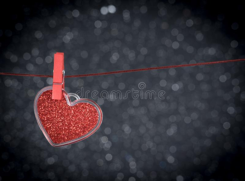 Decorative red heart hanging against dark light bokeh background, concept of valentine day stock photography