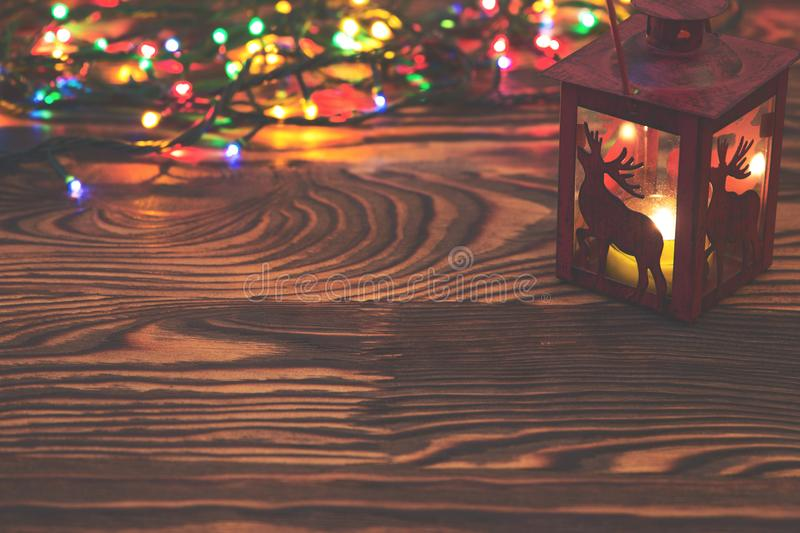 Decorative red metal lantern with a deer cutout lit by a glowing candle with christmas light and copyspace for Christmas. Decorative red metal lantern with a stock photo