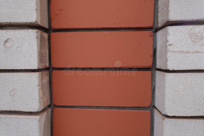 Decorative brickwork made of white and orange bricks. Decorative relief brickwork made of white and orange bricks stock images
