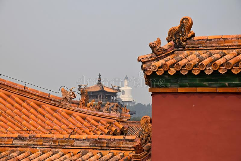 The decorative roofs of Forbidden City with the White pagoda in Beihai park in the background, Beijing, China. royalty free stock image