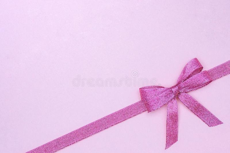 Decorative shiny ribbon with bow on pastel pink background with copy space for text, Top view, Layout.  royalty free stock photography