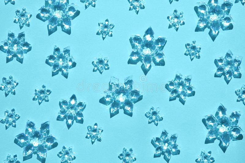 Decorative snowflakes sparse on trendy light blue background. Clear glass decorative snowflakes sparse on trendy light blue background. Minimal christmas concept royalty free stock image