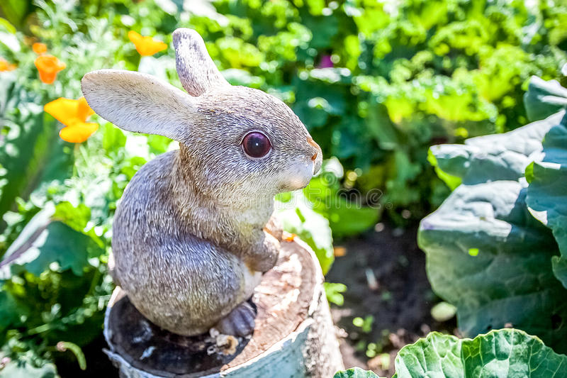 Decorative statuette of rabbit in the garden close up. Decorative statuette of rabbit in the summer garden close up stock photo