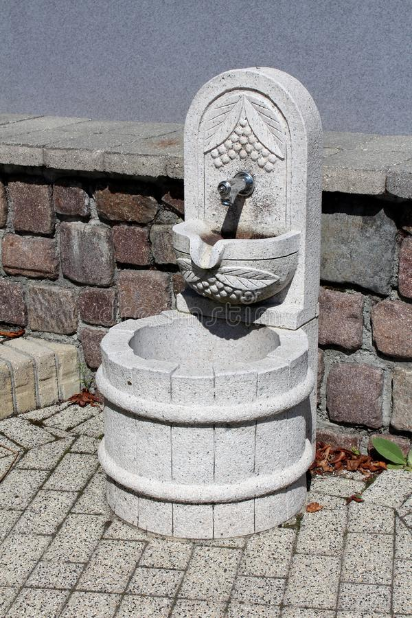Decorative stone drinking water fountain shaped as small well mounted on stone tiles in front of stone wall stock photo
