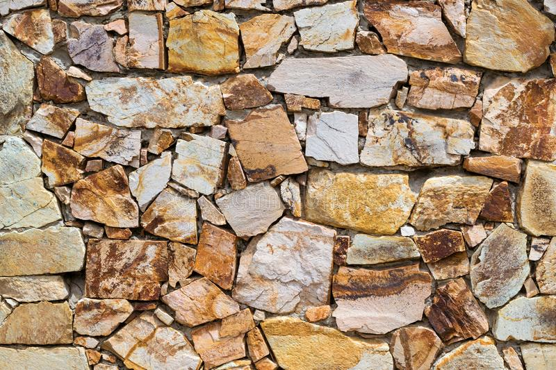Decorative stone wall, Cobble texture with cracks. Decorative stone wall, pieces of rock bonded with cement. Cobble texture with cracks. Mountain of castle San stock photo