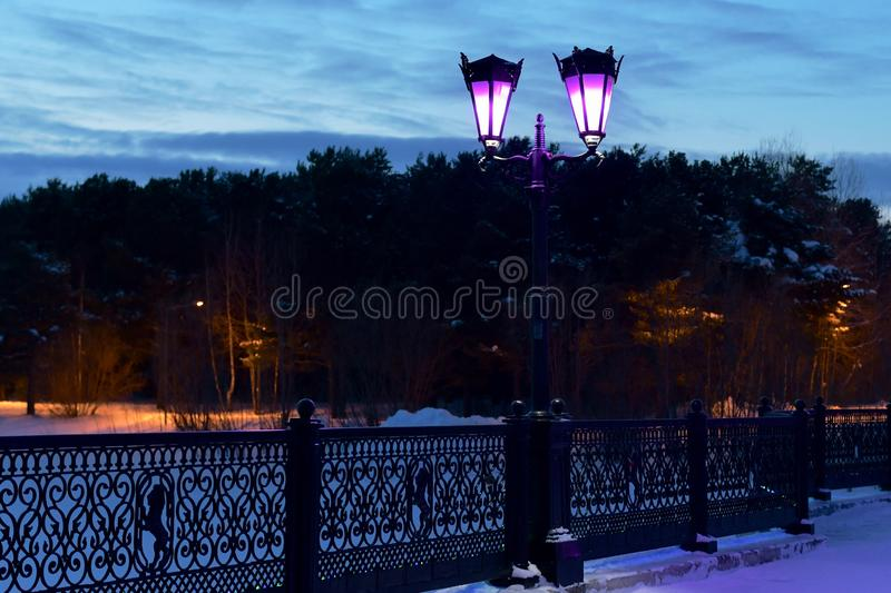 Lanterns on the bridge in the city park. Decorative street fornar on the bridge with a wrought openwork grille. Purple light in the winter twilight of the royalty free stock image