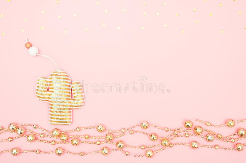 Decorative textile christmas toy cactus, golden garland and stars on pink background. Tropical Christmas or New Year night concept royalty free stock photography