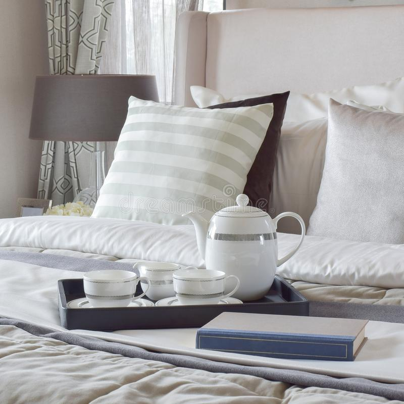 Decorative tray with book and tea set on the bed in modern bedroom. Decorative tray with book and tea set on the bed in the modern bedroom stock images