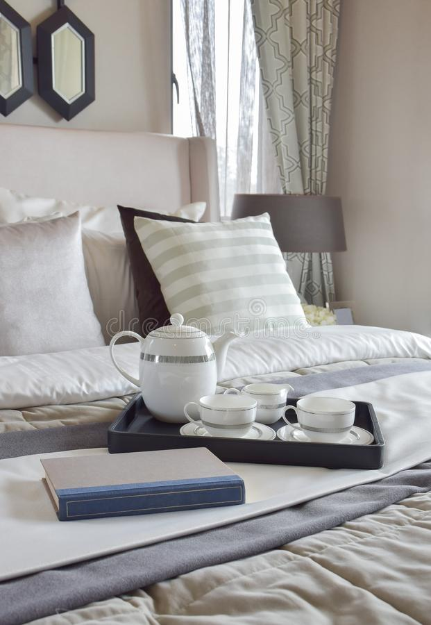 Decorative tray with book and tea set on bed in modern bedroom. Decorative tray with book and tea set on the bed in modern bedroom royalty free stock image