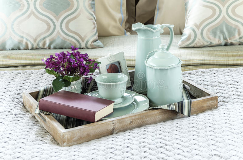 Decorative tray with book, tea set and flower. On the bed royalty free stock photos