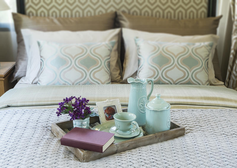 Decorative tray with book,tea set and flower. On the bed royalty free stock photography