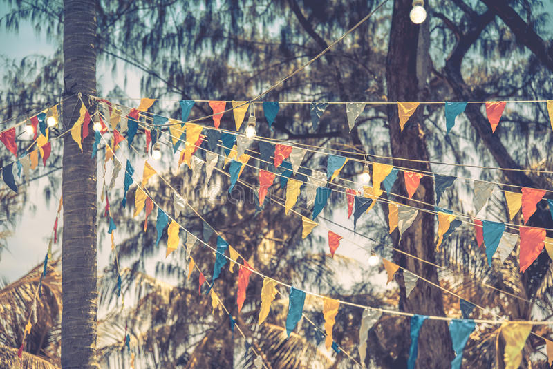 Decorative triangular flags and lamps on trees stock images