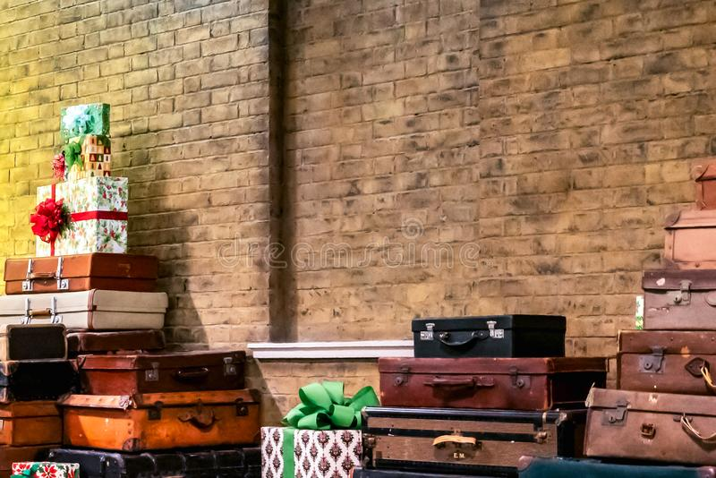 Decorative vintage suitcases and gifts in a brick wall. Decorative vintage retro suitcases and gifts in a brick wall background stock image