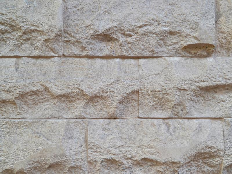 Decorative wall, built of hewn stone slabs of beige color stock photo
