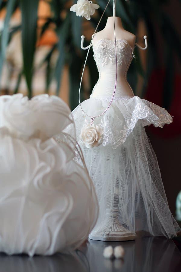 Decorative wedding accessories. Closeup of decorative wedding accessories with white dress stock image