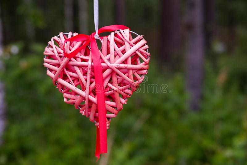 Decorative wedding decoration in the form of a pink or red heart, hanging on a satin ribbon. Symbol of love stock photo