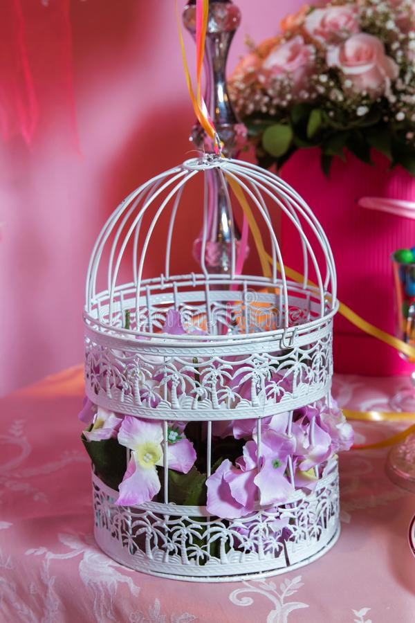 Decorative white bird cage full of pink roses. Candy Bar stock photo