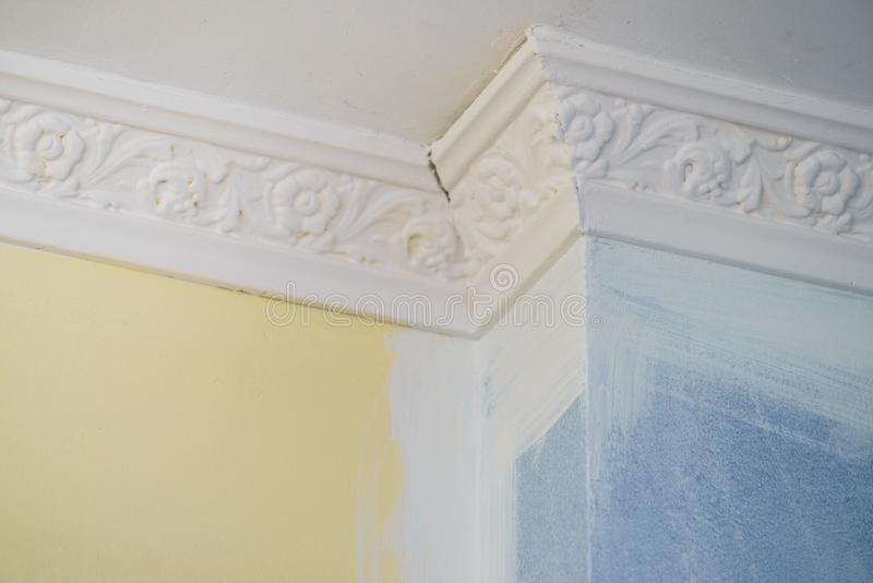 White cornce on wall. Decorative white cornice on blue and yellow wall, home room decor, design, architecture concept royalty free stock photography