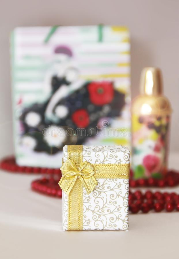 Decorative white gift box with a yellow bow on the background of a parfume and red beads stock image