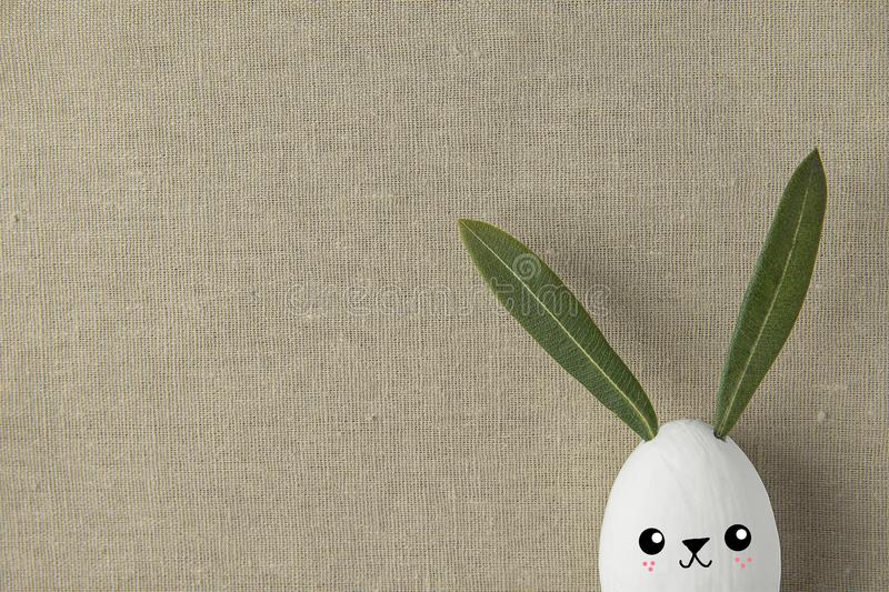 Decorative White Painted Easter Egg Bunny with Drawn Cute Kawaii Smiling Face. Green Leaves Ears. Beige Linen Fabric Background. Holiday Crafts Kids Concept stock photos