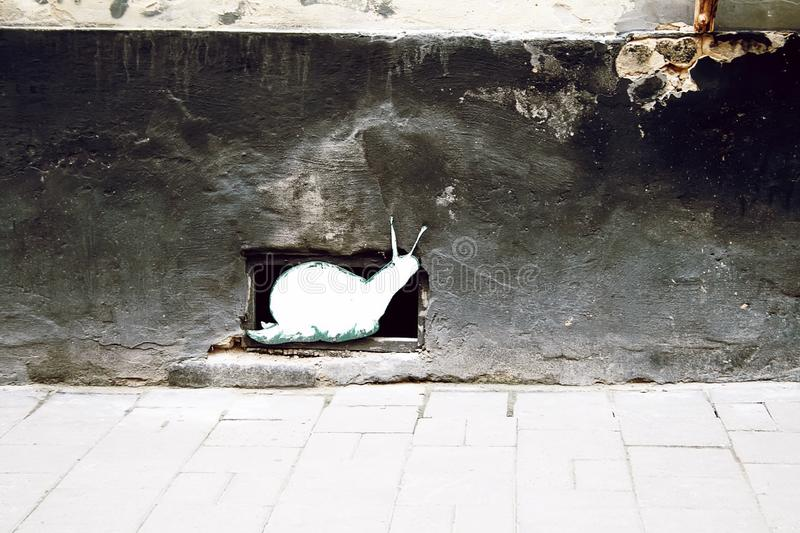 Decorative white snail covering the ventilation hole of the cellar, located at the bottom of the house wall.  stock images
