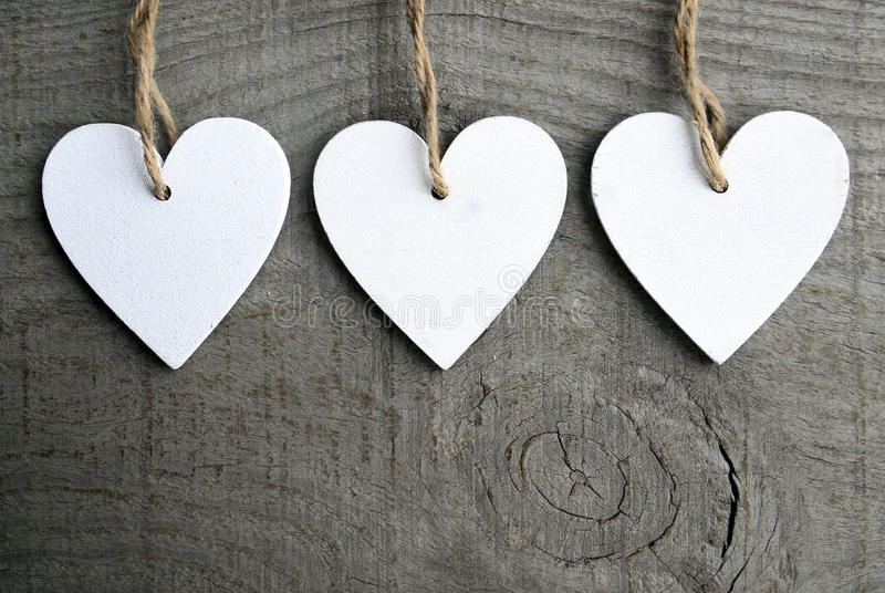 Decorative white wooden Christmas hearts on grey rustic wooden background with copy space. stock photos