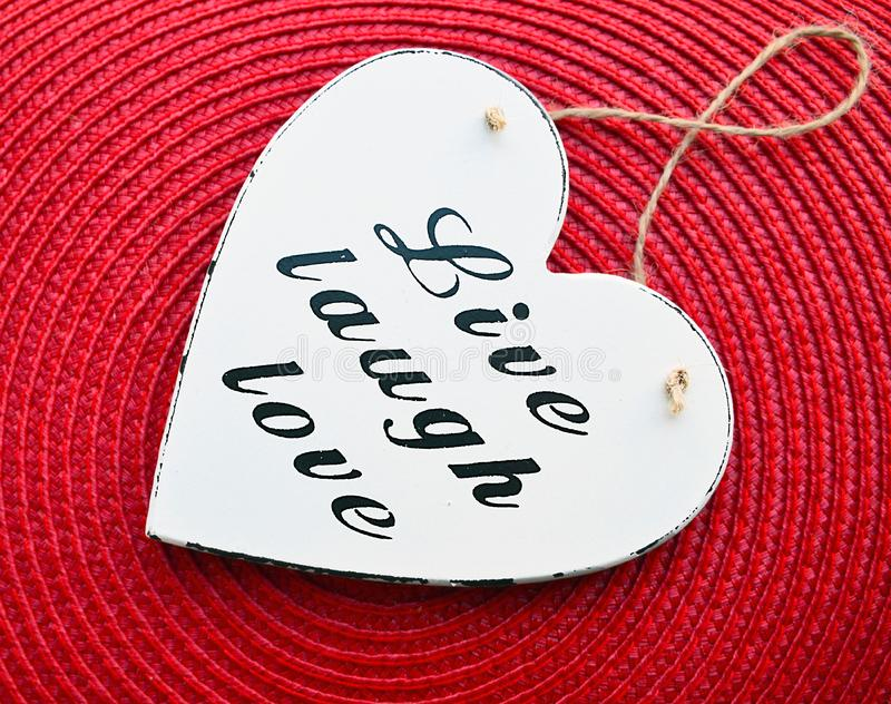 Decorative white wooden heart with the slogan live laugh love on red straw napkin background.Live,Laugh,Love. stock photography